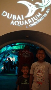 """My kids with their """"superficial smiles' in front of Dubai Aquarium Tunnel"""