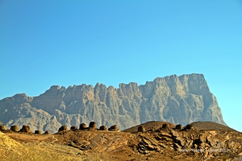 A long row of necropolis of Al Ayn with impressive backdrop of Jabal Misht (Comb Mountain)