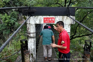 Our taxi driver (with its no-English, Chinese only words) tries to warn us to watch out low hanging bridge gate at Heliu Suspension Bridge
