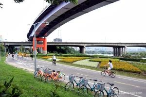 People seen biking on dedicated bicycle lane at Gongguan riverside