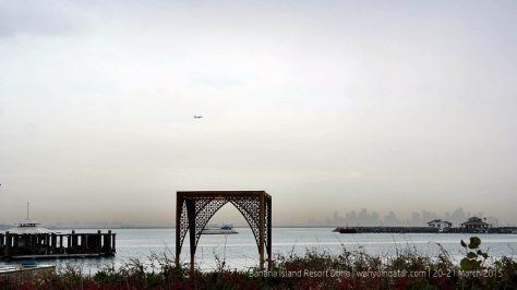 A serene late afternoon: a plane taking off, sea, and Doha skyline